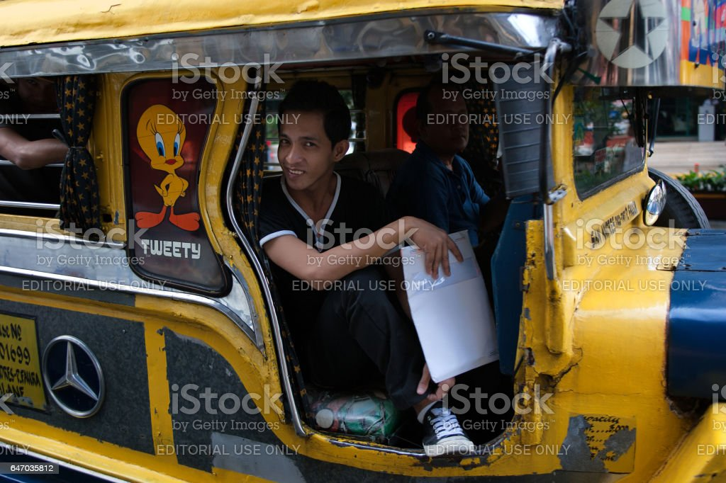 Manila, Philippines - January 25,2012: Man sits in jeepney and moves on a street of Manila stock photo