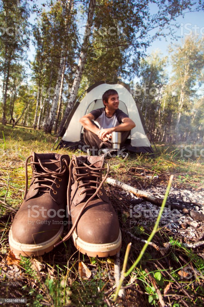 leather brown shoes and man with cup near the campfire in the tent,...