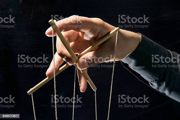 Concept on a theme: the manipulation, the dictator, dependency, slavery, etc. Dictator's arm holds  strings for manipulation on black background.
