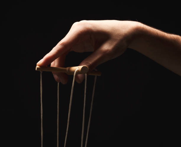 Manipulators hand with marionette string isolated on black Male hand with marionette strings on black isolated backgorund. Manipulation, control and dictatorship concept, copy space puppet stock pictures, royalty-free photos & images