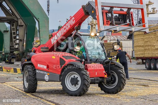 VARNA, BULGARIA September,19,2016; Manitou Maniscopic four-wheel drive forklift tractor loading hay bales onto a trailer