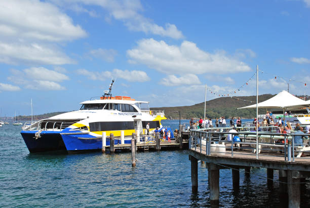 Manly Fast Ferry boat at Manly wharf ready to pick up passengers and depart to Sydney Cirqular Quay Sydney, Australia - October 11, 2015: Manly Fast Ferry boat at Manly wharf ready to pick up passengers and depart to Sydney Cirqular Quay in the summer noon. depart stock pictures, royalty-free photos & images