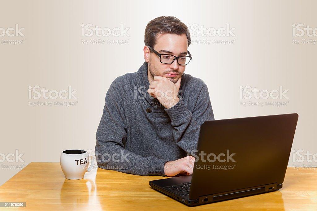 Mann arbeitet im Sitzen an einem Laptop stock photo