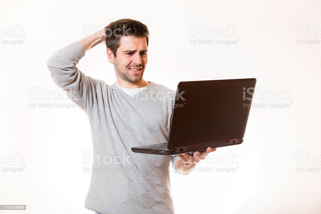 Mann drückt verzweiflung aus beim Blick auf seinen Laptop stock photo