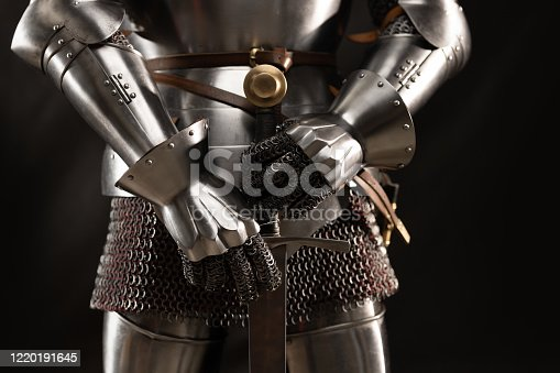 Mannequin man with a beard in a helmet and armor of a knight posing on a black background