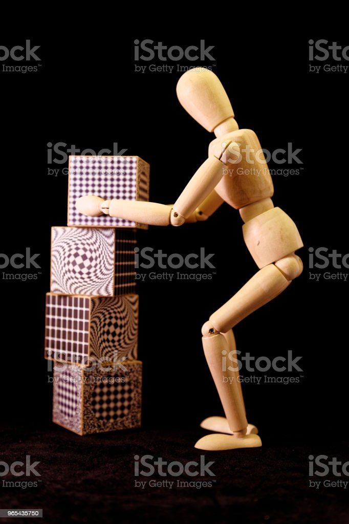 mannequin organizing large cubes one of top of the other royalty-free stock photo