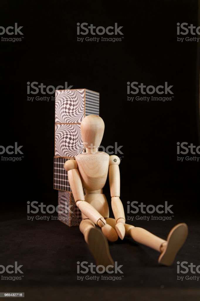mannequin sitting by  large black and white cubes/boxes one of top of the other zbiór zdjęć royalty-free