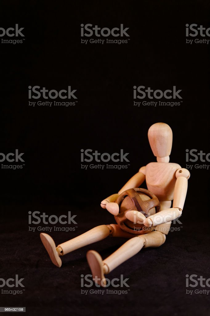 Mannequin sitting on the floor, puzzled, holding an unsolvable wooden ball zbiór zdjęć royalty-free