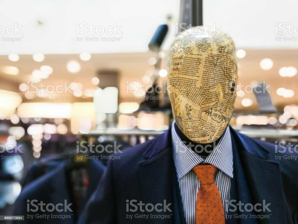 Mannequin with head wrapped in newspaper article modeling smart suit, shirt and tie in department store stock photo