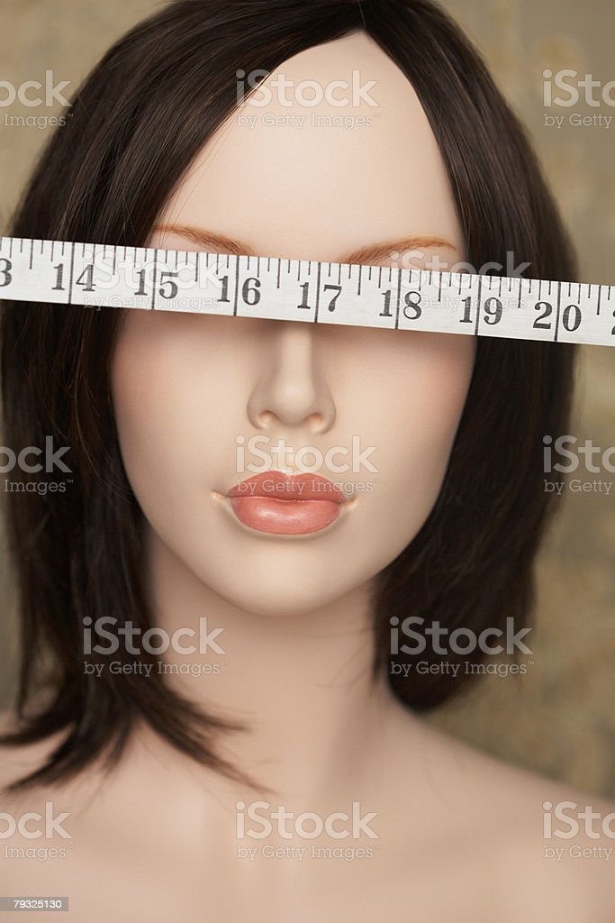 Mannequin with tape measure over eyes 免版稅 stock photo