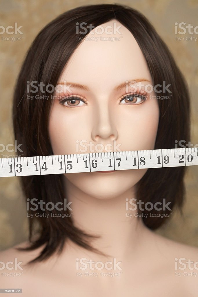 Mannequin with tape measure over mouth royalty-free stock photo