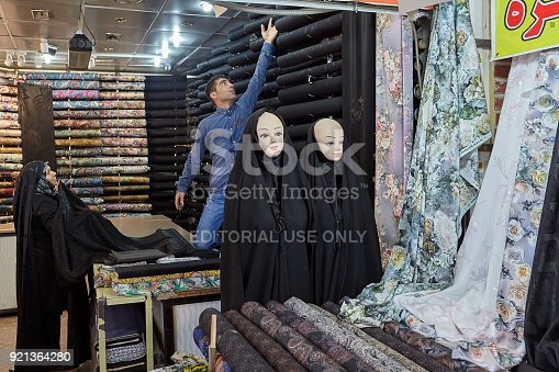 Tehran, Iran - April 29, 2017: An elderly Muslim woman chooses a cloth for a religious veil in the department of fabrics of the Tehran Grand Bazaar.