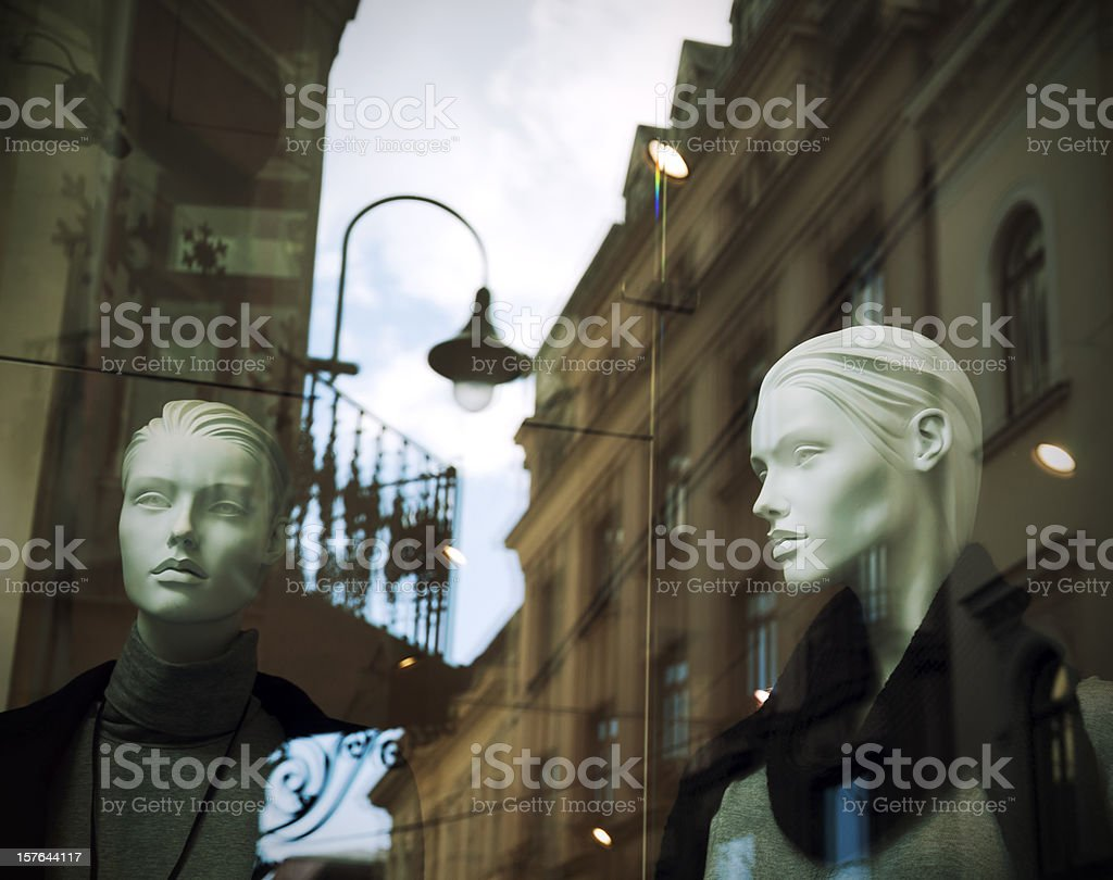 Mannequins in shop window with street reflection royalty-free stock photo