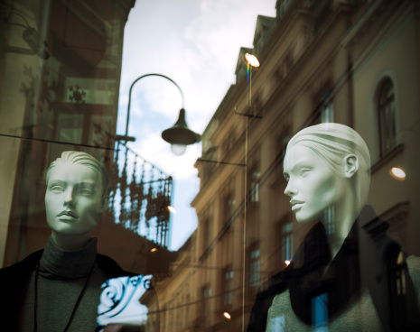 Mannequins in shop window with street reflection