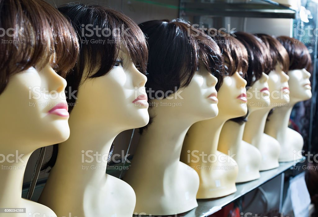 Mannequins with brown-haired and brunet style wigs on shelves - foto stock