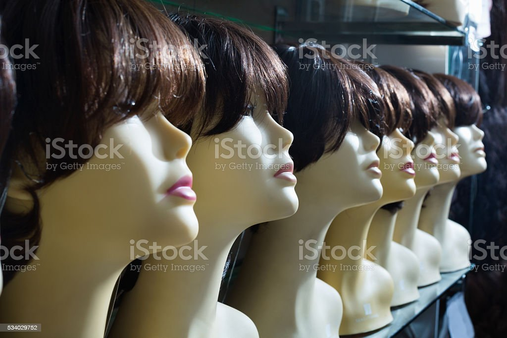 Mannequins with brunet style wigs on shelves stock photo