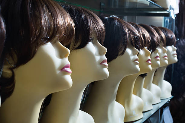 mannequins with brunet style wigs on shelves - row of heads stock photos and pictures