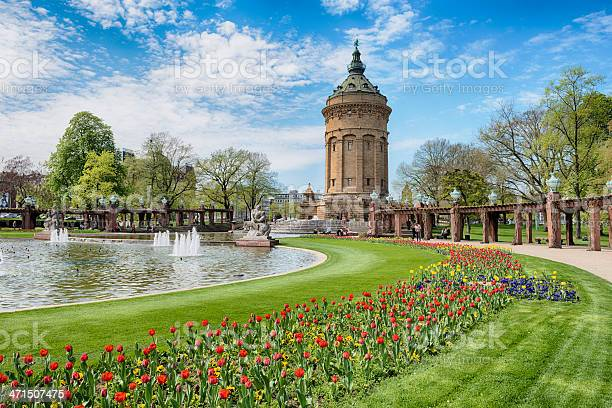 Mannheim, Germany - April 23, 2013: Old water tower in Mannheim. The tower is one of the landmarks in  Mannheim and was erected in 1886 by the architect Gustav Halmhuber. People are enjoying a nice spring day by relaxing in the park.