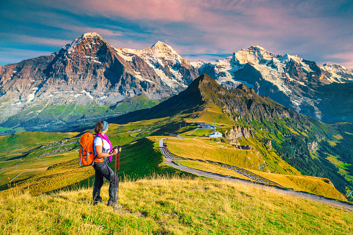 Famous Mannlichen tourist resort and cable car station. Backpacker hiker woman enjoying the view with high snowy mountains at sunset, Grindelwald, Bernese Oberland, Switzerland, Europe