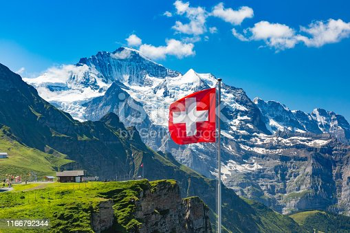 Swiss flag waving and tourists admire the peaks of Jungfrau mountain on a Mannlichen viewpoint, Bernese Oberland Switzerland