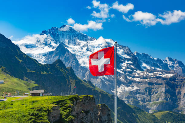 Mannlichen viewpoint, Switzerland Swiss flag waving and tourists admire the peaks of Jungfrau mountain on a Mannlichen viewpoint, Bernese Oberland Switzerland swiss alps stock pictures, royalty-free photos & images