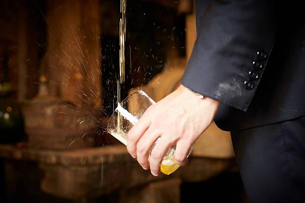mano sosteniendo vaso de sidra que está siendo escanciada - ncaa photos et images de collection