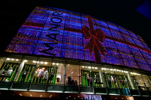 Lugano, Ticino, Switzerland - 25th November 2020 : View at night of the Manor department store decorated for Christmas the day after the terror attack happened inside