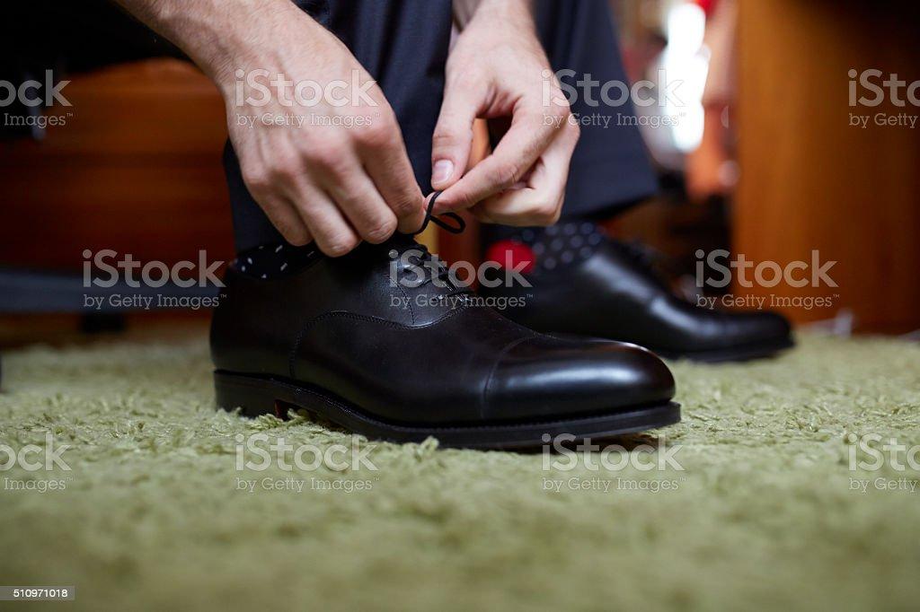 Manos de hombre atando zapatos de vestir negros stock photo