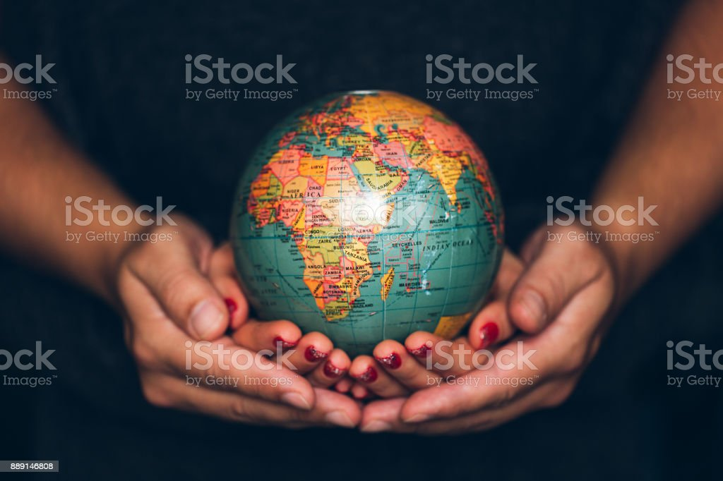 Man's and Woman's hands holding Earth stock photo
