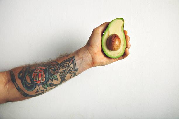 man's arm with half of avocado - essen tattoos stock-fotos und bilder