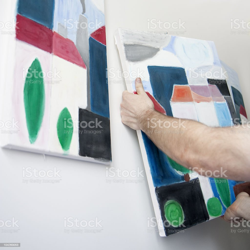 A man's arms hanging a painting beside another similar one  stock photo