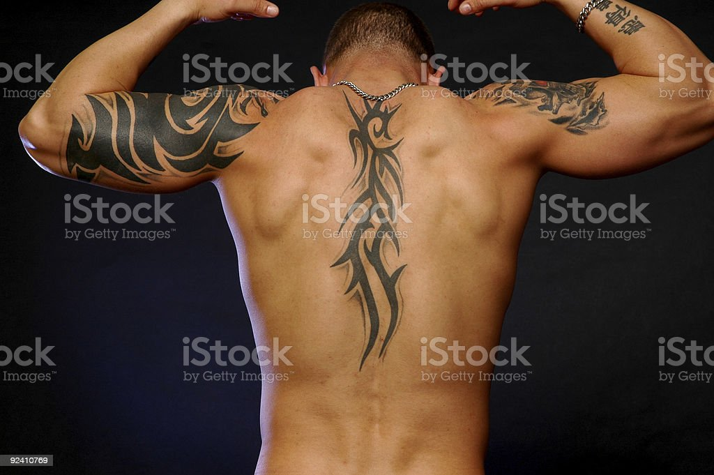 Man's back showing tribal tattoos on arms and back stock photo