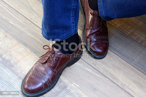 Close-up of man´s feet with shiny brown shoes