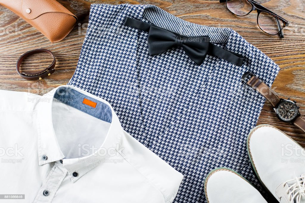Man's classic clothes outfit flat lay with formal shirt, vest, bowtie, shoes and accessories stock photo