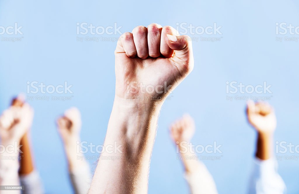 Man's clenched fist raised in triumph or defiance, against blue stock photo