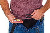 istock Man's crotch while holding potency pills 1131314187