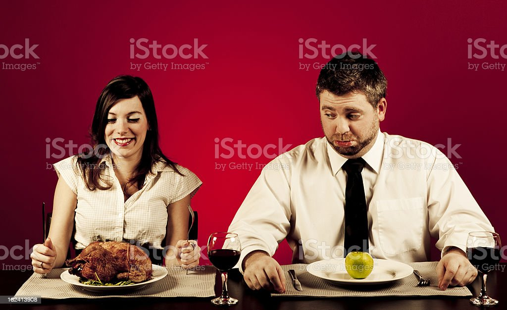 Young man looking at his girlfriend\'s meal with envy. A little of...