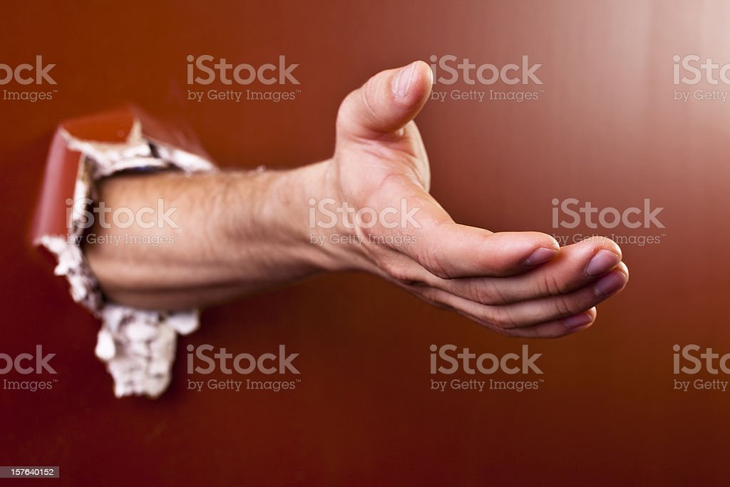 Man's extended hand coming through wall. stock photo