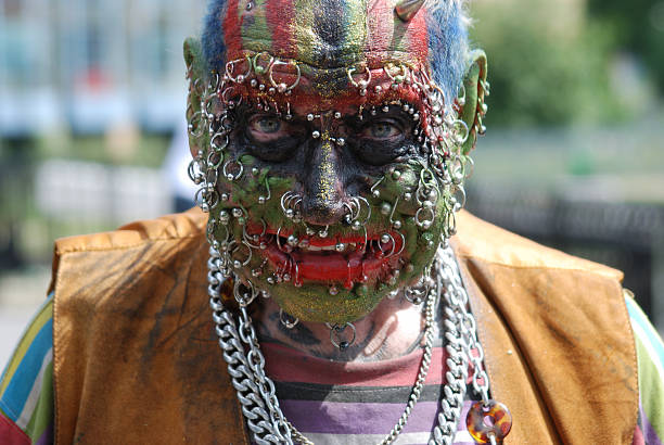 man's face covered in piercings and face paint - nose ring stock pictures, royalty-free photos & images