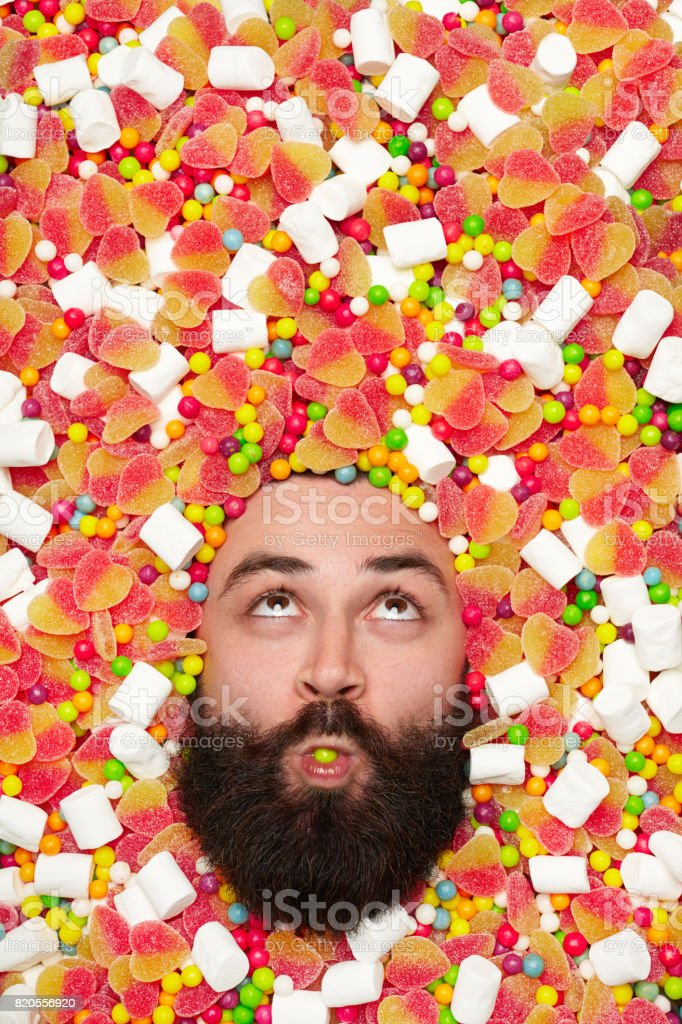 Man's face surrounded with sweet stuff stock photo