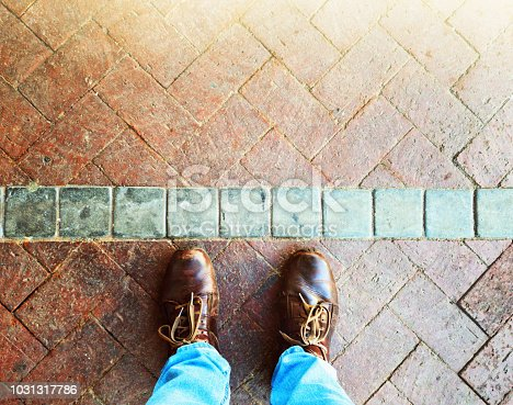Looking down at a man's feet on the edge of a line in a floor of brick paving marking a psychological barrier.