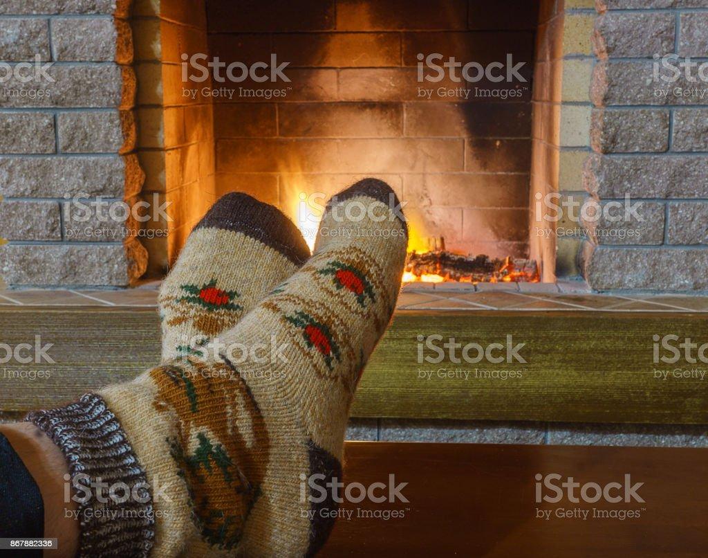 e1275702cc58f Pieds de l'homme en chaussettes ; devant la cheminée, dans maison de  campagne