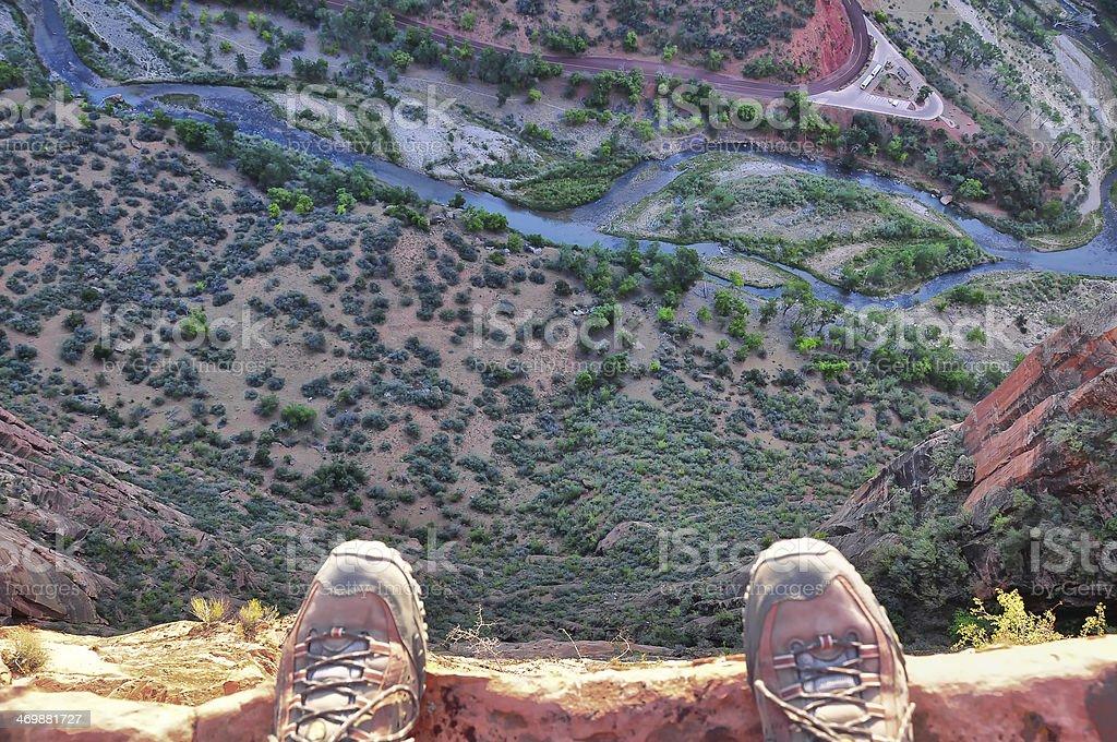 Man's feet on the edge of rock cliff Man's feet on the edge of rock cliff Aerial View Stock Photo