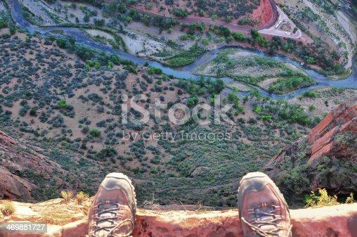 Man's feet on the edge of rock cliff