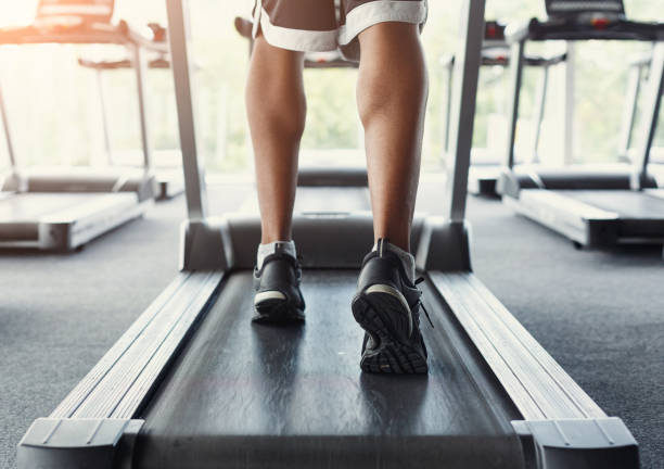 Man's feet on treadmill in fitness club, healthy lifestyle stock photo