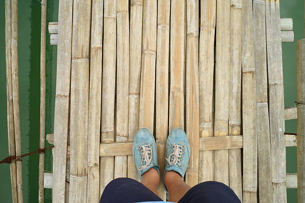Man's feet point of view on suspension bridge – Foto