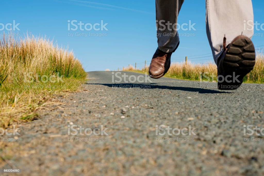 Man's feet running along an empty country road. royalty-free stock photo