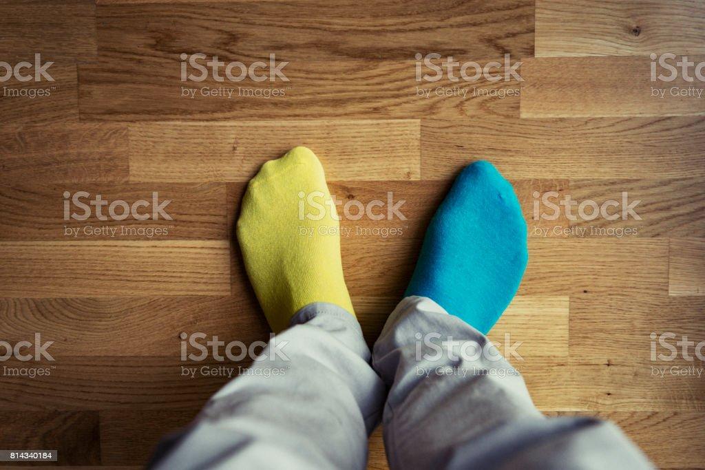 Man's feet with odd socks stock photo