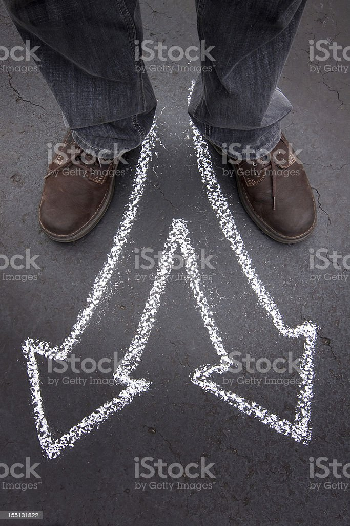 Man's feet with two chalk pointing arrows stock photo