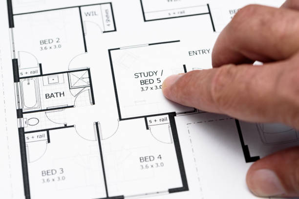 Mans finger pointing to house plans stock photo